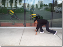 A woman posing with her hands on the ground as if she was about to race poses in front of a window with mannequins in racing motions