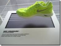 An athletic shoe rests on a table. The shoe is light green and there is a light gray swoosh on the side. The table has a display that has 2 words. The first is Nike, the second is illegible.