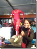 A woman poses as if she was running in front of a mannequin positioned in a running stance.