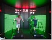Two men utilize a treadmill with a display above both of them with various numbers.