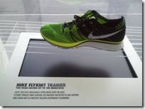 An athletic shoe rests on a table. The front portion is green, the back is black, and there is a white Nike swoosh on the side. The table has a display that reads Nike Flyknit Trainer