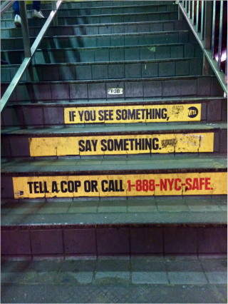 A set of stairs in a public train terminal. There is legible text on the stairs that reads If you see something say something. Tell a cop or Call 1-888-NYC-SAFE
