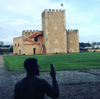 A man in shadow takes a picture on his phone of a stone castle