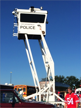 A police stand rises above tailgater. The stand reads City of Buffalo Police. There is a man in red jersey with the number 64 in front of it.