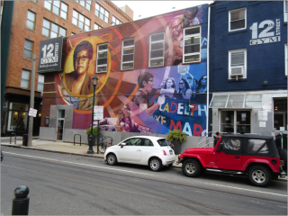2 buildings with signs reading 12th Street gym. The larger building has a mural on the side. On the left of the mural there is a portrait of a woman with glasses and short hair framed in an orange circle. The bottom right of the mural shows that same woman speaking to a group of protestors. The top right of the mural shows two men in an intimate embrace