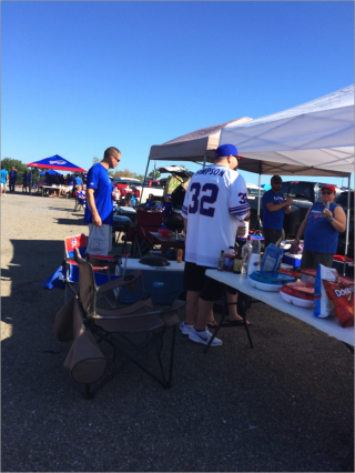 A group of people are tailgatin, they are all wearing Bills' clothing.