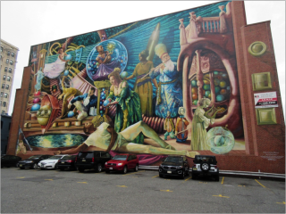 A large building with a mural on the side. The mural depicts well dressed people in various stages of lounging in a Grecian style. The people depicted are white and black