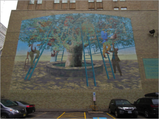 A large building with a mural on the side. The mural depicts a large tree. Men with ladders are climbing the ladders and looking through the branches.