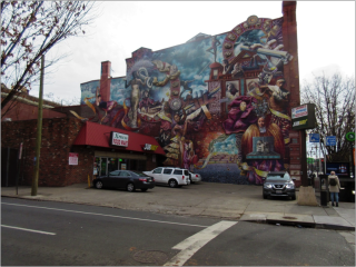 A large building rises over a Subway and Express Food Mart and their subway. The large building has a mural. The mural depicts various black people in the arts. Some are performing gymnastics, some are dancing, and some are in very fashionable dresses.
