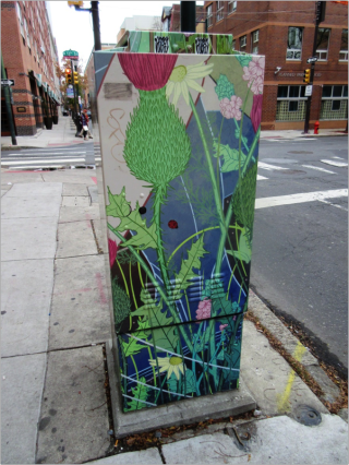 An electrical box, about the height of a human, is on the sidewalk with a mural on its back. The mural depicts flowers, ladybugs, and grass.