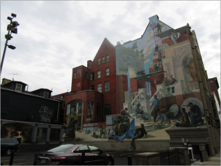 A large red bricked building with a mural on its side. The mural depicts the outside of a building that is undergoing construction. There are various statues and people outside the building. Men are working on the building. They are on scaffolding and painting, and on the grounds mixing concrete.