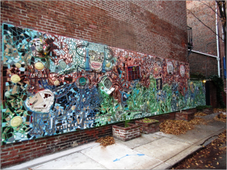A mural on the side of the building. The mural is composed of a mosaic of glass pieces. At various points there are drawn images of heads, human and dog, where the glass pieces have formed a body. The top of the mural has red glass, and the bottom has blue and green. Also at the bottom is text reading While Everything is Happening.