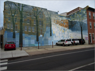 A large building with a mural on its side. The mural depicts a snowy scene with tress without leaves and buildings identical to the one the mural is painted on