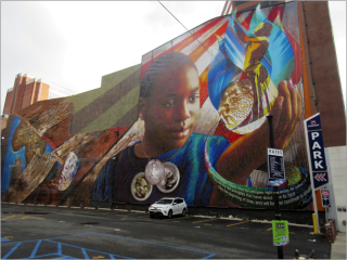 A large industrial building has a mural on its side. The mural depicts a young black child with his hand up. In his hand are are a glowing sphere, a black woman in a thoughtful pose, and a blue flower, he is looking at those things in wonder. From the sphere there is text coming out. Around his neck there is a necklace with 3 lockets, one shows Abraham Lincoln, one shows Frderick Douglas, and one shows a coin of a man praying. On the left hand side of the mural there are a ship's planks, a broken mask, and part of a world map showing Africa.