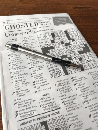 A newspaper folded to the crossword puzzle. The puzzle is mostly filled out and many clues are crossed out