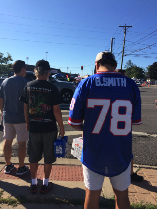 Men outside waiting to cross the street on a sunny day. One of the men has a Bills jersey on, it reads B. Smith, number 78