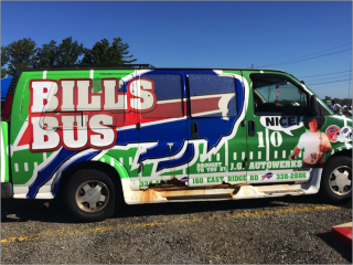 A large 15 person van has been painted with the image of a football field and with the Buffalo Bills logo. There is text at the bottom that says Brought to You by J.G. Autowerks, 160 East Ridge Rd, 338-2886. On the passenger side front door, there is a man in a white shirt and a wig with a text bubble that says Nice.