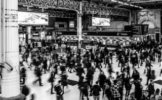 Grayscale-photography-of-people-walking-in-train-station-735795
